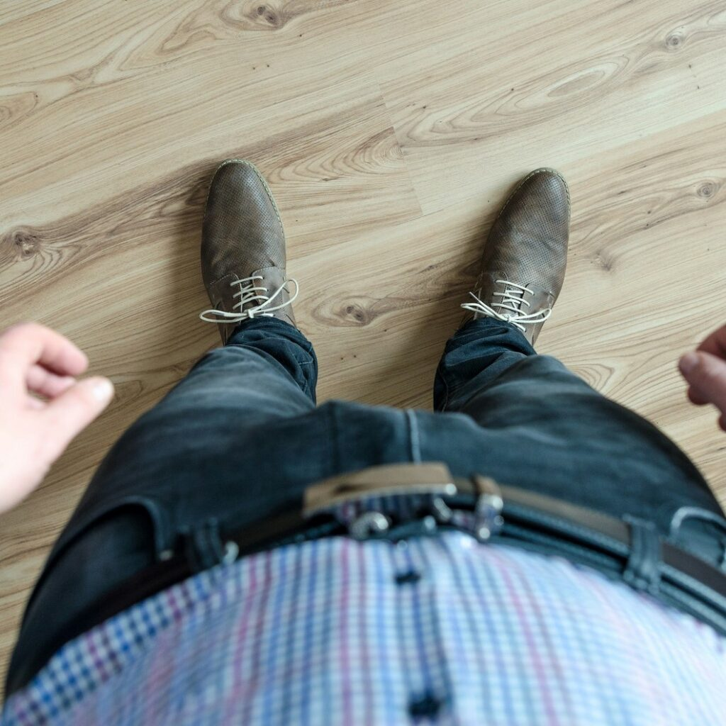Looking down from above at a man wearing jeans and brown shoes