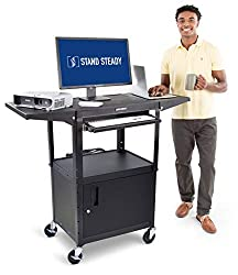 Man stands beside mobile workstation with laptop, monitor and projector