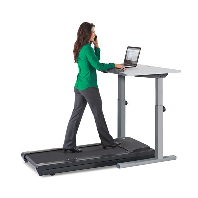 Woman walking on LifeSpan TR1200 treadmill whilst working on her laptop