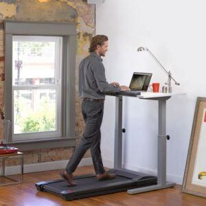 Man walks on the lifespan TR800 treadmill whilst working on his laptop