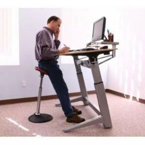 Man leaning into the Mobis 2 seat whilst working at a standing desk