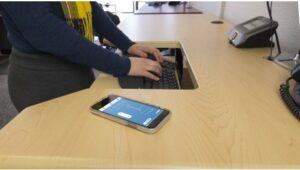 Woman working on tilting keyboard tray with smartphone to the right