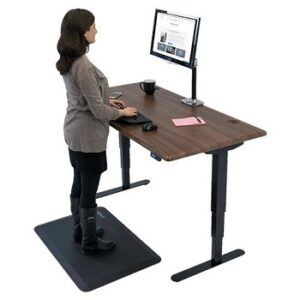 Woman standing on anti-fatigue mat as she works at her standing desk