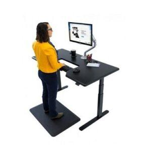 Back view of a woman standing at an iMovR Lander desk with built-in SteadyType keyboard tray