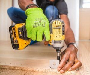 Electric screwdriver attaching bracket to a sheet of MDF