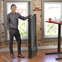 Man standing with walking treadmill in upright position