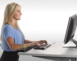 Woman at standing desk typing onto keyboard and looking ahead to a monitor