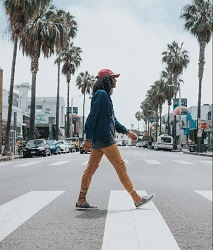 Man walks across a zebra crossing with palm trees and buildings in the background