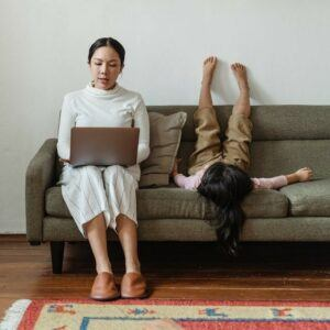 Woman working on laptop whilst sitting on sofa next to a child