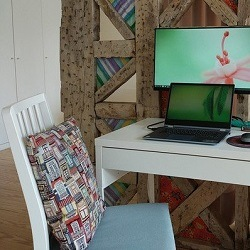 Laptop and monitor on desk with chair and cushion in foreground
