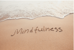 Beach scene with the word mindfulness written in the sand