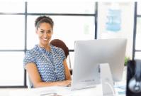Woman sat as desk in front of laptop