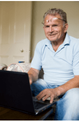 Gentleman of advanced years smiles as he types onto a laptop