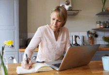 Woman with laptop and notebook working from the kitchen counter