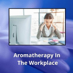 """Woman with head in hands at desk with text underneath reading """"Aromatherapy in the Workplace"""""""