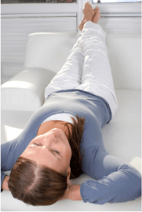 Woman laying on sofa with hands behind her head, relaxing
