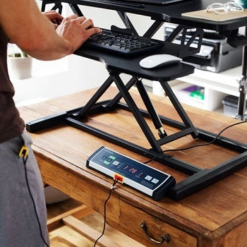 Standing desk converter in raised position with the DT3 console on the main desktop