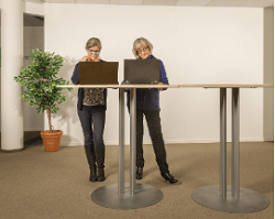 2 women with laptops work at a standing desk