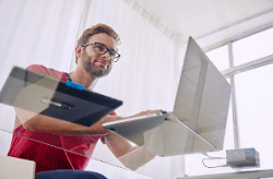 Man using laptop on glass topped desk