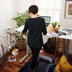 Back view of woman working at desk whilst walking on a treadmill