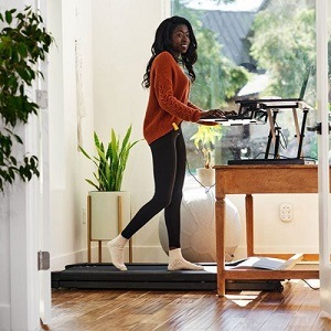 Woman walking on treadmill whilst working from a standing desk converter