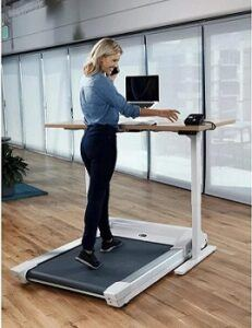 Woman walking on treadmill whilst working at standing desk