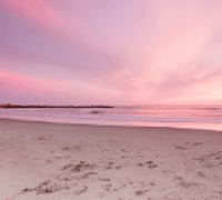 Pink and blue sky above a deserted sandy beach