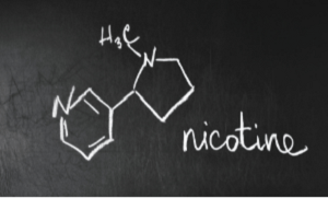 Chalk on a blackboard with the name and chemical formula of nictoine