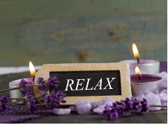 """Lavendar sprigs and aromatherapy candles surround a small chalk board with the word """"relax"""" written on it"""