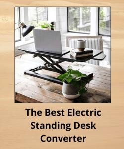 Wooden desktop supports an electric standing desk converter